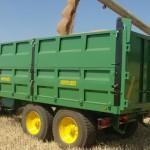 Remolque agrícola tándem de laterales cosechando con tractor John Deere